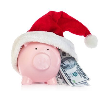 christmas bonus: Piggy bank with Santa Claus hat and money on white background