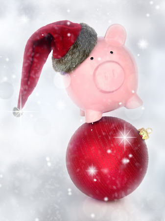 Piggy bank on a Christmas ball in a glittery background photo