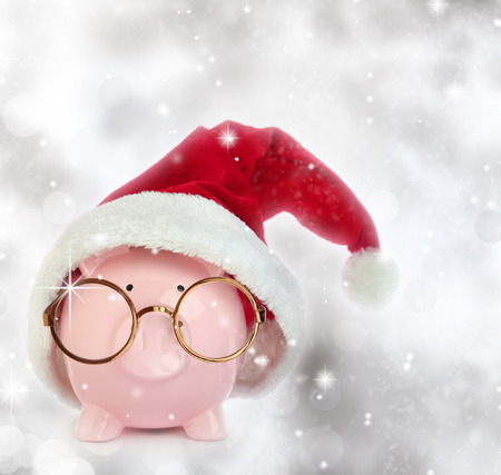 Piggy bank with Santa Claus hat and eyeglasses in a glittery background photo