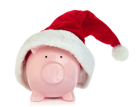 Piggy bank with Santa Claus hat on white background photo