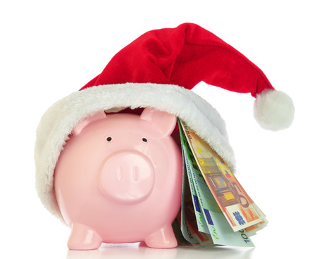 Piggy bank with Santa Claus hat and money on white background photo