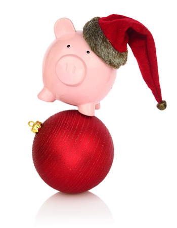 Piggy bank with Santa Claus hat balancing on a Christmas ball photo
