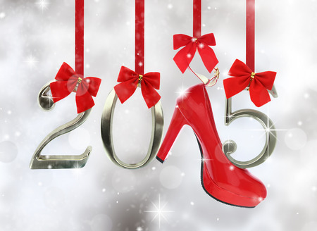 High heel shoe and 2015 number hanging on red ribbons in a glittery background photo