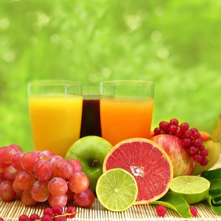 grape juice: Fresh fruit and three glasses full of juice