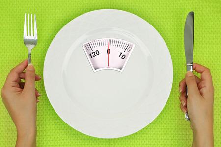 Hände und Teller mit Waage auf dem Tisch