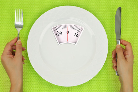 dishes: Hands and plate with weighing scale on the table