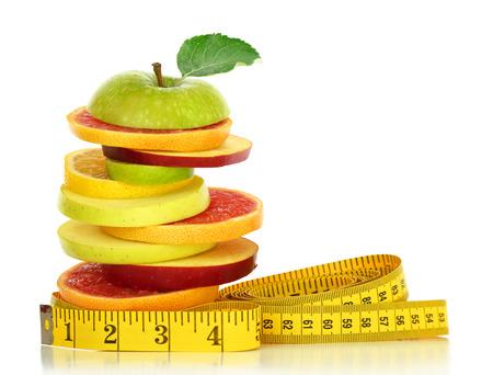 cinta metrica: Rodajas de frutas frescas y cinta métrica aislados en blanco