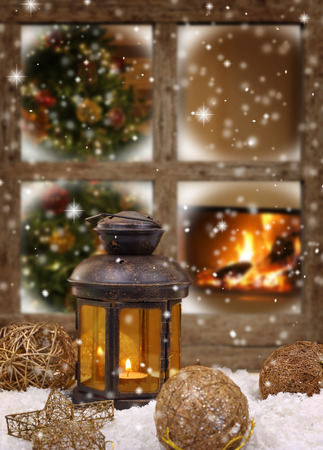 Christmas lantern and ornaments on snow in front of a window photo