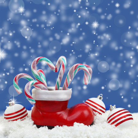 Christmas candy canes in santas boot on snow photo