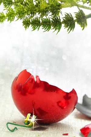 Broken ornamento rojo de Navidad bajo rama del árbol