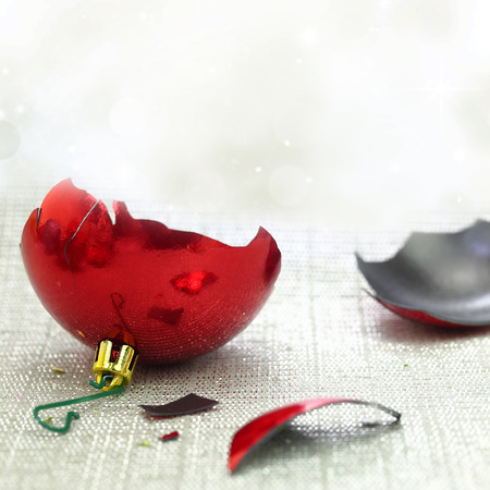 Broken red Christmas ornament with bokeh background