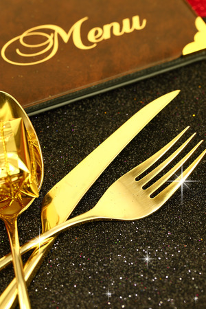 Christmas golden cutlery and restaurant menu on festive background
