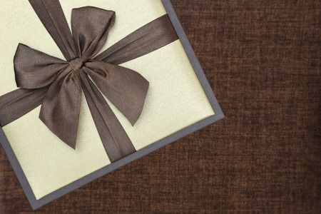 Gift box with ribbon on brown background