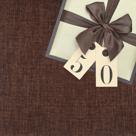 number 50: Gift box with ribbon and number 50 on brown background
