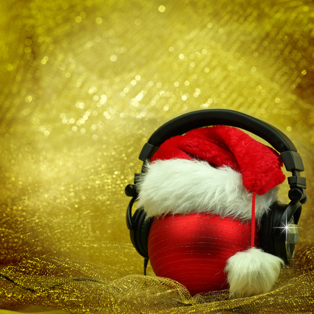 Christmas ball with headphones in glittering background Stock Photo