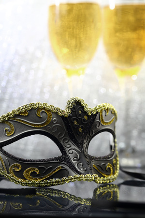 Vintage carnival mask in front of champagne glasses photo