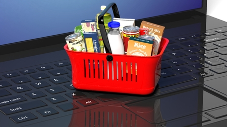 hand basket: Shopping hand basket full with products on laptops keyboard