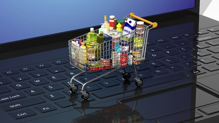 Full with products supermarket shopping cart on black laptops keyboard Stockfoto