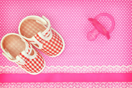 polka dot background: Baby shoes and pink pacifier on polka dots background with copy space