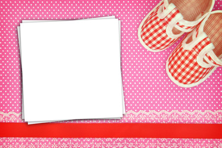 Baby shoes and blank cards on polka dots background photo