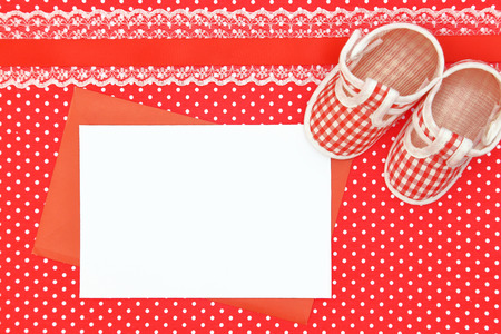 Baby shoes and blank card on polka dots background photo