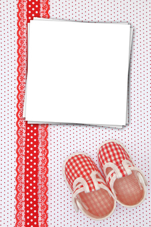 Baby shoes and paper cards on polka dots background photo