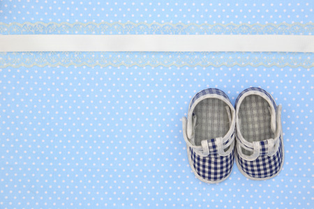 Baby shoes on blue polka dots background photo