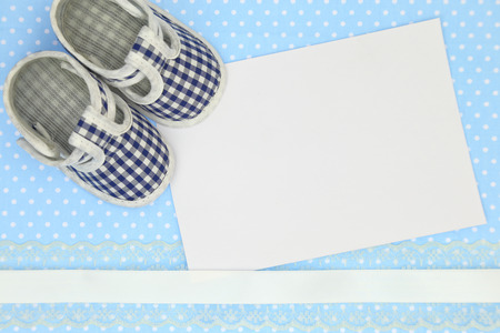 Baby shoes and blank card on blue polka background Stock Photo - 35916459