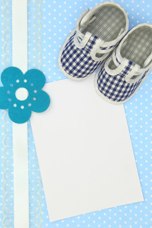 Baby shoes and blank card on blue polka background photo