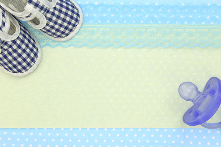 Baby shoes and blue pacifier on polka dots background with copy space