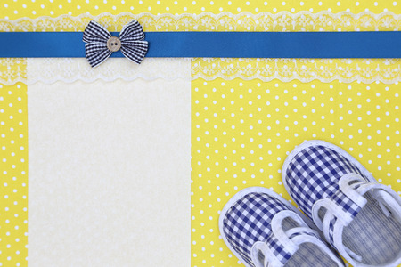 Baby shoes and blank banner on yellow polka background Foto de archivo