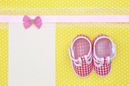 Baby shoes and blank banner  on polka dots background photo