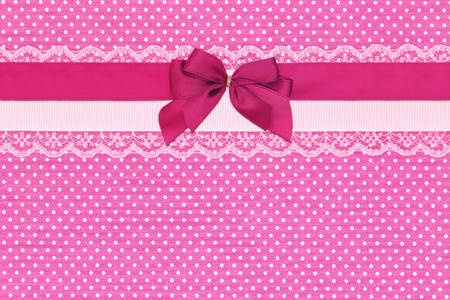 polka dots background: Pink polka dot textile background with ribbons and bow