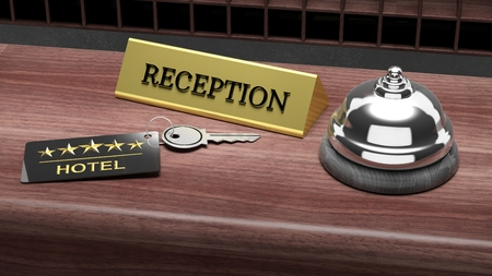 Hotel reception bell and and key on reception wooden desk photo