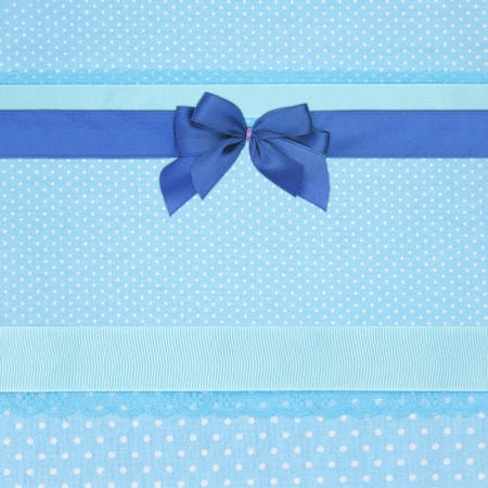 Blue retro polka dot textile background with ribbons and bow