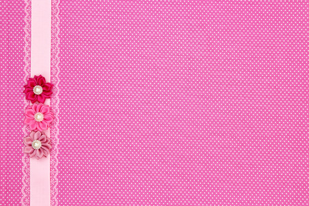 Pink polka dot textile background with ribbon and flowers
