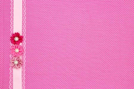 Roze stip textiel achtergrond met lint en bloemen Stockfoto