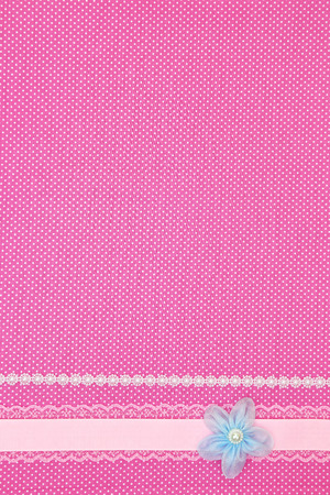Pink polka dot textile background with ribbon and flower