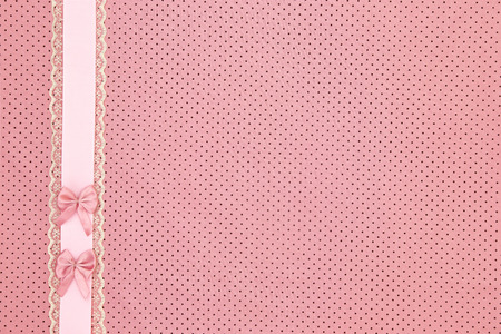 Pink polka dot textile background with ribbon and bows