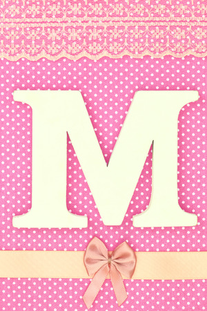 Wooden letter M on polka dots background photo