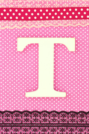Wooden letter T on polka dots background photo