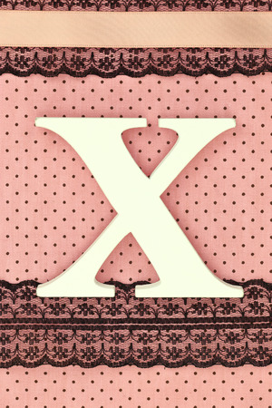 Wooden letter X on polka dots background photo