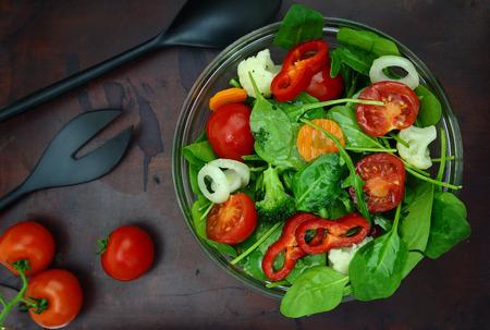 ensalada: Bol de ensalada colorida fresca con tenedor y cuchara en superficie de madera
