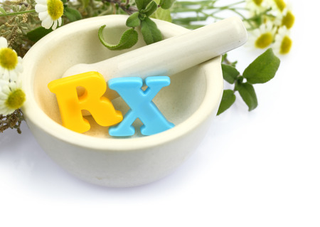 rx: Mortar with fresh herbs and colorful letters RX isolated on white
