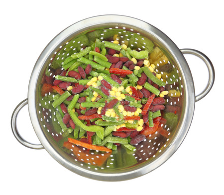 Colander with frozen mixed vegetables isolated on white photo