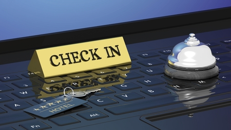 Hotels room key, check in and bell on laptops keyboard
