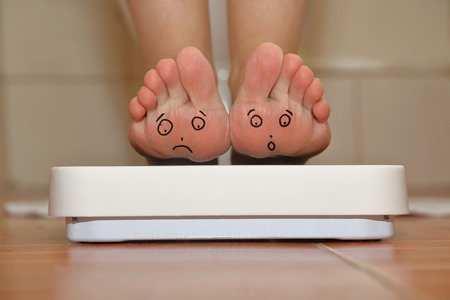 obese person: Feet on bathroom scale with hand drawn sad cute faces