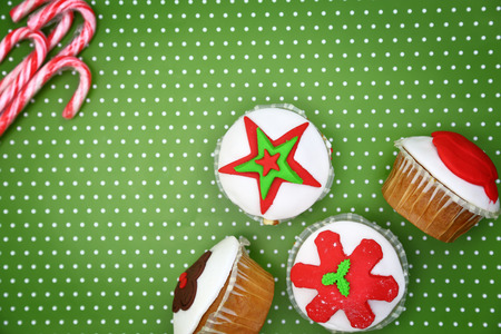 christmas cupcakes: Festive Christmas cupcakes and candy canes on green background