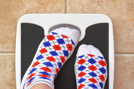 weight control: Womans feet on bathroom scale. Diet concept
