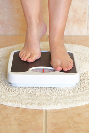 overeat: Womans feet on bathroom scale. Diet concept